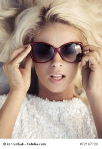 Fine portrait of the lady putting on the sunglasses